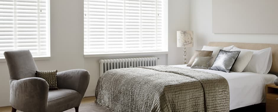 White taped faux wood blinds in bedroom